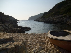An artistic view of avlaki beach in paxos with a small boat parked on the land.